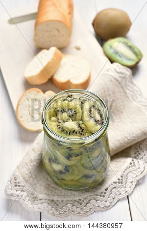 Preserved kiwi in glass jar and sliced bread