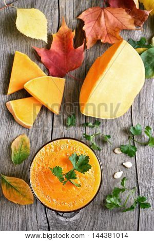 Pumpkin juice raw slices and colorful autumn leaves on wooden background top view