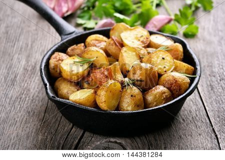 Fried potato in frying pan on wooden background