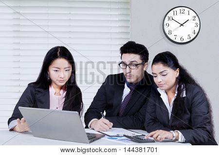 Group of multi ethnic business partner using laptop in the office while working together to make a plan and strategy