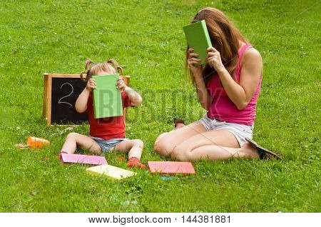 Mom and daughter reading a book together outdoors