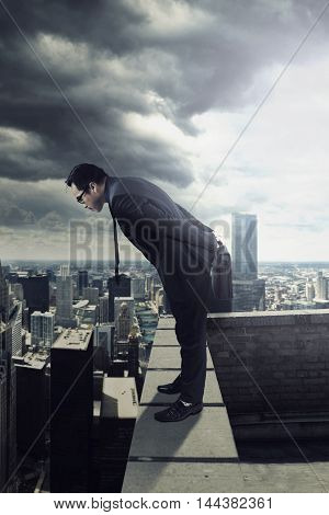 Young businessman standing on the building roof while carrying bag and looking down