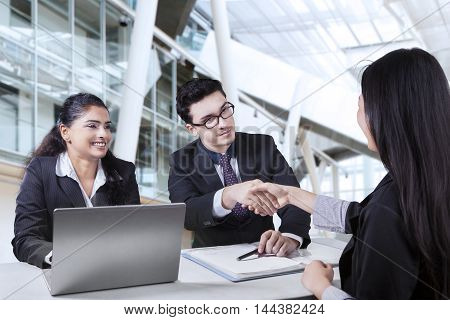 Young businessman and his partner shaking hands with new female worker in the office