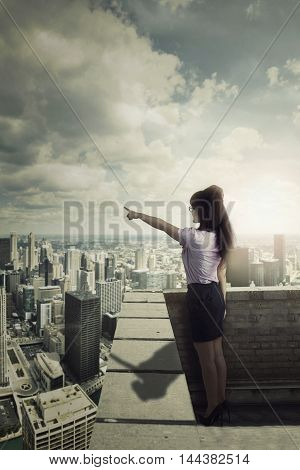 Young businesswoman standing on the building roof while pointing at the sky