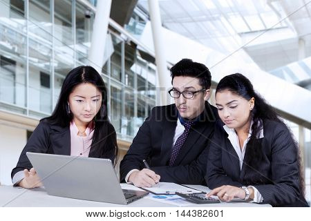 Group of busy business team sitting in the office while discussing business plan with laptop