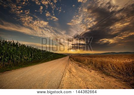 Sunset road and fields of corn and grain. Moravian landscape Boskovice.
