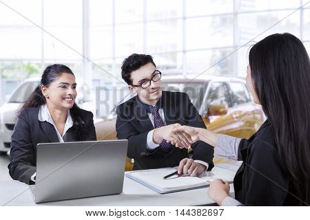 Portrait of two car seller smiling and shaking hands with their buyer in the showroom