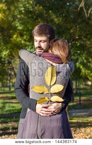 Loving couple hugging in the park while holding yellow autumn leaves