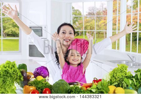Cheerful little girl and her mother raise hands in the kitchen with fresh vegetables on the table