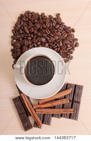 Coffee cup and chocolate on wood background
