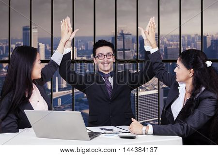 Three multi ethnic business people celebrating their victory by clapping hands together in the office