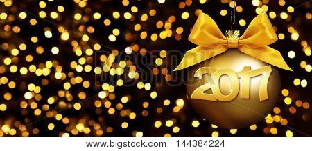 christmas ball and 2017 text with golden satin ribbon bow on blurred gold lights background