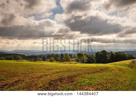 Sun rays shining through the clouds on landscape. Moravian landscape Sulikov.