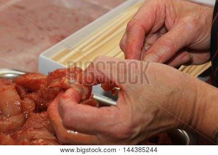 a poulterer prepairing barbecue meat on sticks