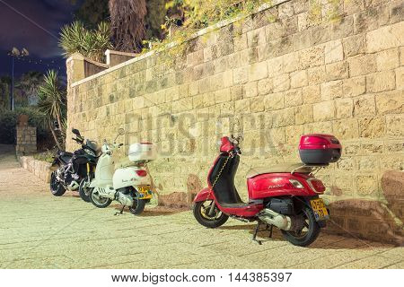 TEL AVIV, ISRAEL - JUNE 4, 2015: Mopeds parked at night in the old town