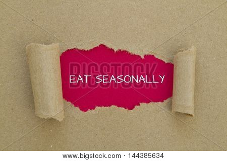 Eat seasonally message written under torn paper.