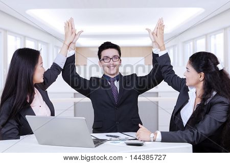Cheerful multi ethnic employees celebrating their success in the office while raising hands up together