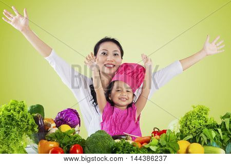 Photo of joyful mother and her daughter raise hands together with vegetables on the table