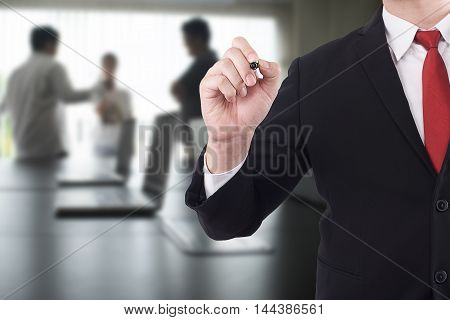 businessman with black marker in the meeting room background.