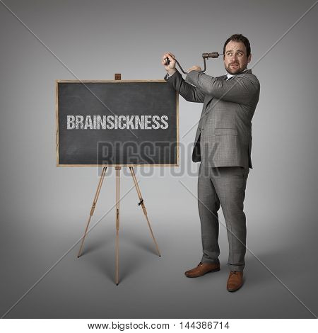 Brainsickness text on blackboard with businessman drilling his head