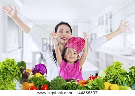 Cheerful mother and her daughter raise hands together in the kitchen with fresh vegetables on the table
