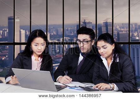 Group of three multi ethnic workers discussing in the office while using laptop computer together on desk