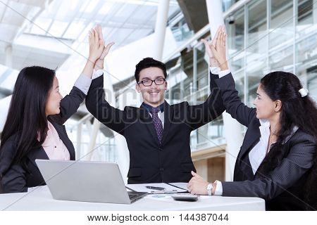 Three multiracial employees celebrating their victory by raising hands up together with laptop on desk shot in the office