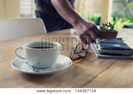 cup of coffee on old wooden desk. Simple workspace or coffee break in morning.