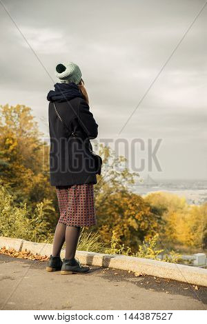 girl in autumn park looks into the distance