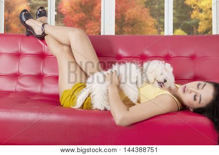 Beautiful young asian woman sleeping on the sofa while hugging her puppy at home