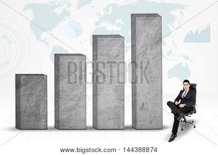 Male entrepreneur sitting on the office chair near the growing finance graph with world map background
