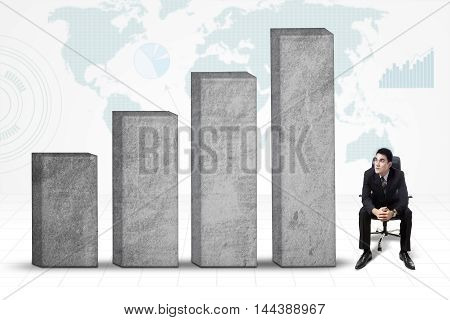 Male entrepreneur looking at growing business graph while wearing business suit and sitting on the office chair