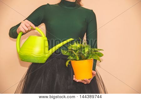 girl holding a flower pot and a Watering can
