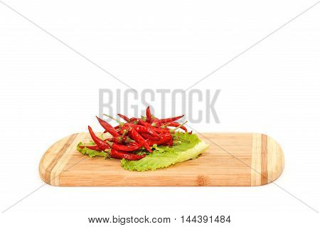 Close view of red hot chili peper lying on green salad isolated over white background