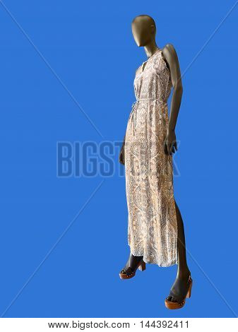 Beautiful summer dress on female mannequin isolated on blue background. No brand names or copyright objects.