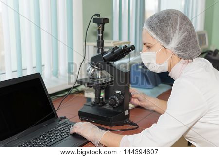 Women scientists exploring the biological sample by modern electron microscope in a laboratory