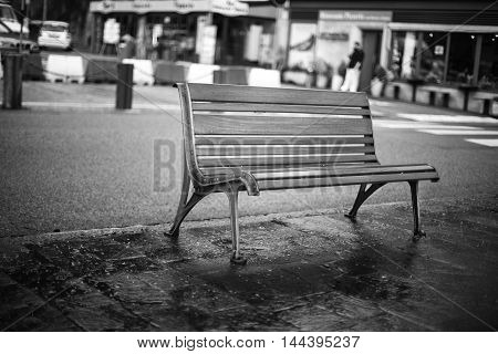 Bench on the street beside the road after the rain.
