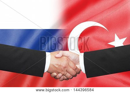 isolated two businessman shakehand over russia and turkey flag