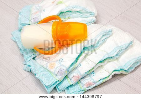 Accessory set for Baby disposable diapers on gray background tree items for baby care. Lay diaper nappy parent taking care of a baby. safe baby ear sticks breast milk in the bottle