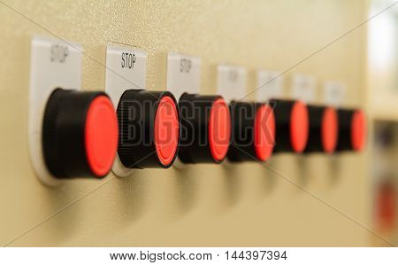Red stop buttons on control panel of machine control.