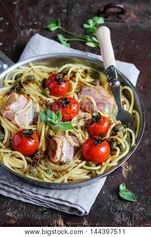 Cooked pasta spaghetti with bacon and roasted cherry tomatoes in a pan on a wooden table, selective focus