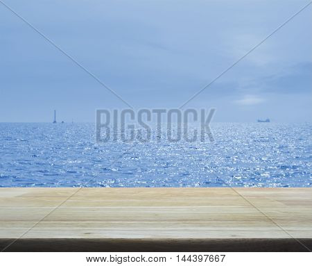 Empty wooden table over boat silhouette with sea and blue sky
