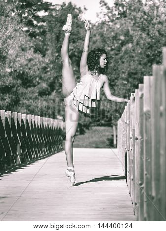Latin woman dancing ballet in a park with leg raised above his head monochrome