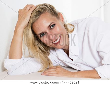 blond woman in a white shirt is lying in bed and smiles