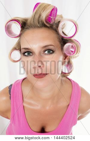 blond woman with pink curlers is smiling