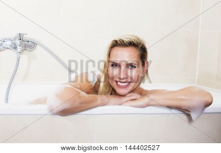 blond woman sitting in bathtub and smiling