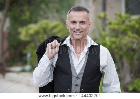 portrait of a businessman standing outside and smiles