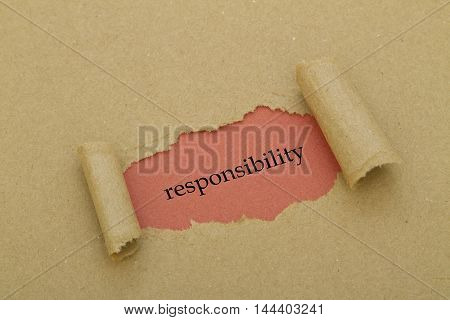 Responsibility word under brown torn paper .