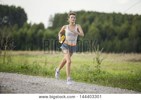 Runner woman with bottle of water. Beautiful fit female fitness model training and working out outside in summer at part of healthy lifestyle.