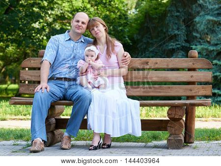 happy family portrait with baby girl on outdoor, sit on wooden bench in city park, summer season, child and parent